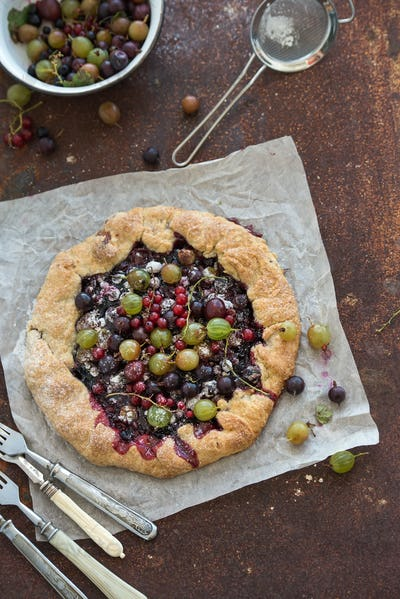 Crostata or galette pie with fresh garden berries over grunge rusty metal background, top view