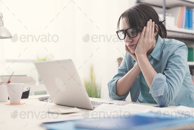 Bored woman working with her laptop