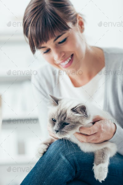 Smiling woman cuddling her cat