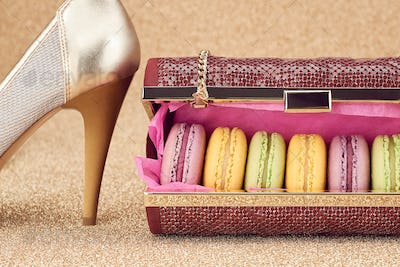 Macarons in fashion handbag, heels on gold.Vintage