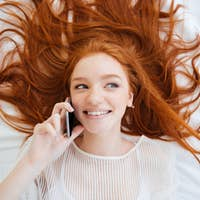 Cheerful playful woman talking on cell phone in bed