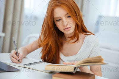 Redhead woman doing homework