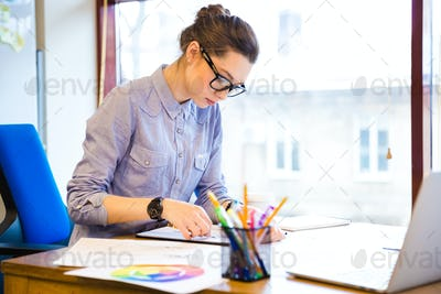 Concentrated woman fashion designer drawing sketches in office