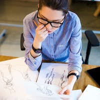 Pensive woman fashion designer sitting and looking at sketches