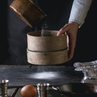 Sifting flour by female hands