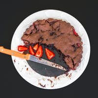 Chocolate strawberry cake with fresh strawberries on a white cer