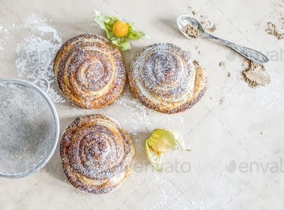 Cinnamon buns with sugar powder and ground cherry