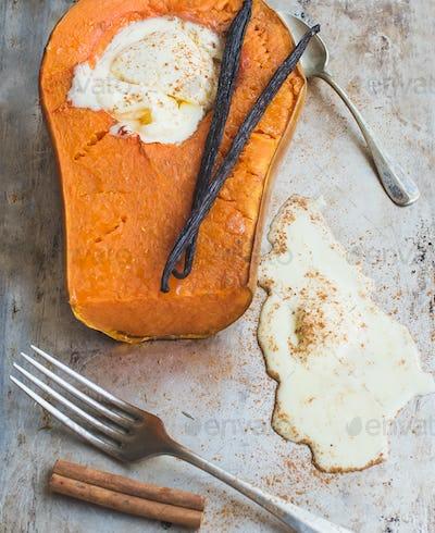 Backed pumpkin half with a scoop of vanilla ice-cream, vanilla s