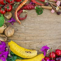 Mediterranean fruit, vegetables and flowers on a rough wooden bo