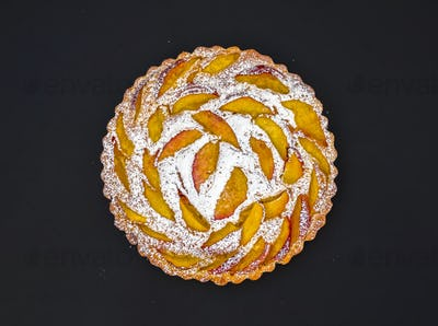 Peach pie with sugar powder on dark