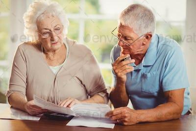 Senior couple counting bills at home