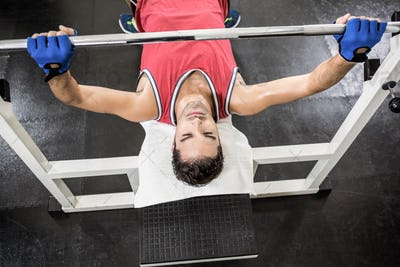 Muscular man lifting barbell on bench at the gym