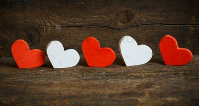 Red and white hearts on old shabby wooden background