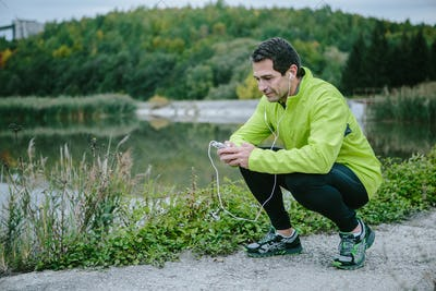 Runner with smart phone at the lake resting, green trees