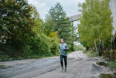 Man running on an old road in green nature.