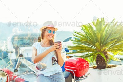 Trendy woman drinking takeaway coffee near her red moped on the