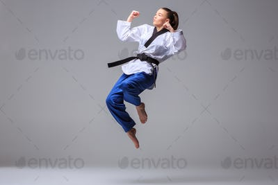 Photo-023The karate girl in white kimono and black belt training karate over gray background.