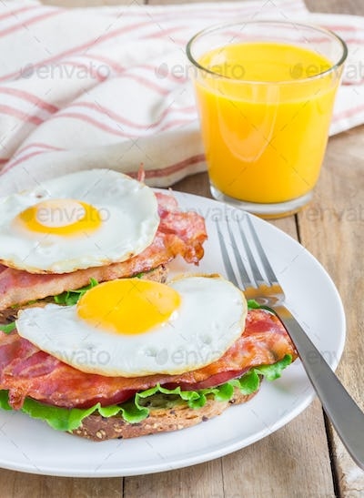 Open face sandwich with egg, bacon, tomato and lettuce