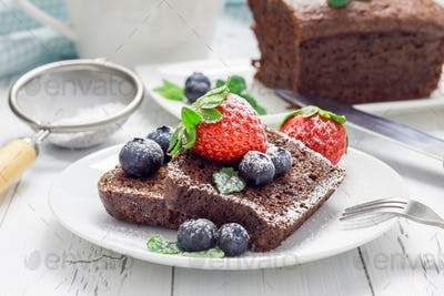 Freshly baked homemade chocolate banana bread (cake), decorated with berries