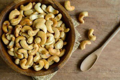 Fried cashew nuts with wooden spoon on sackcloth