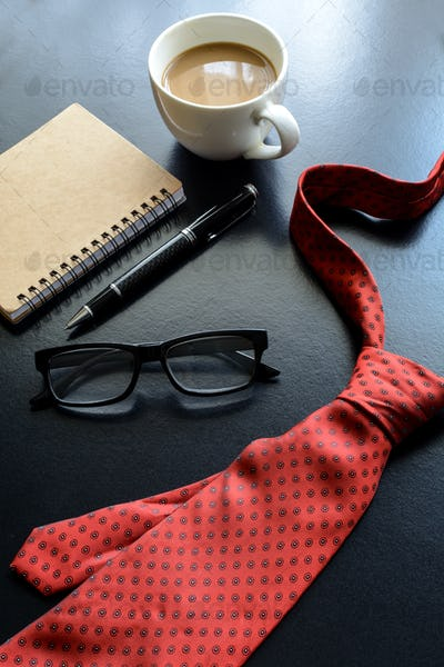 Necktie and cup of coffee on office desk