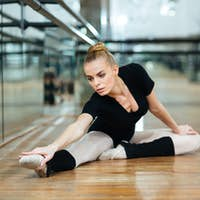 Ballerina doing stretching exercises in ballet class