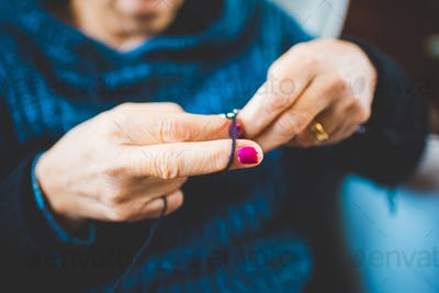 Close up on the hands of a woman knitting with knitting needles