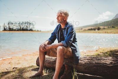 Mature man sitting on a log near lake
