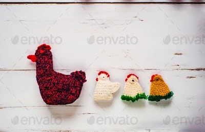 Three crocheted Easter chickens and knitted hen,white wooden background