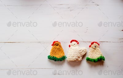 Three colorful crocheted Easter chickens against white wooden background