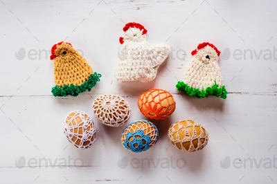 Colorful crocheted Easter chickens and eggs against wooden background
