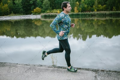 Man at the lake running against green cloudy nature
