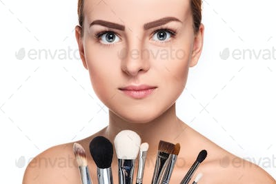 Beautiful female eyes with bright blue make-up and brush