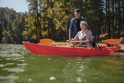 Senior woman getting kayaking lessons from a man