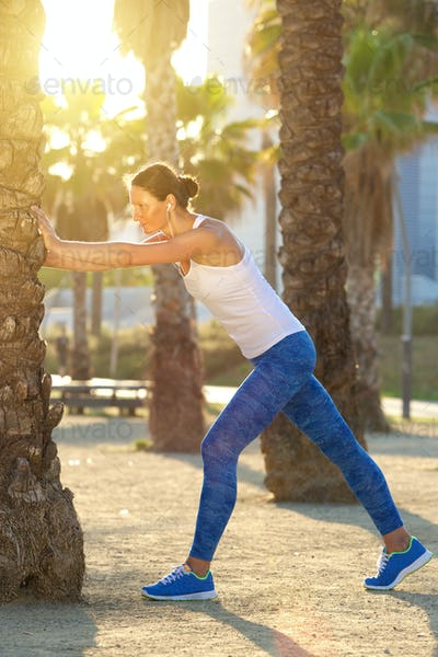 Active woman stretching muscles after workout