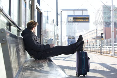 Young man waiting for train at station