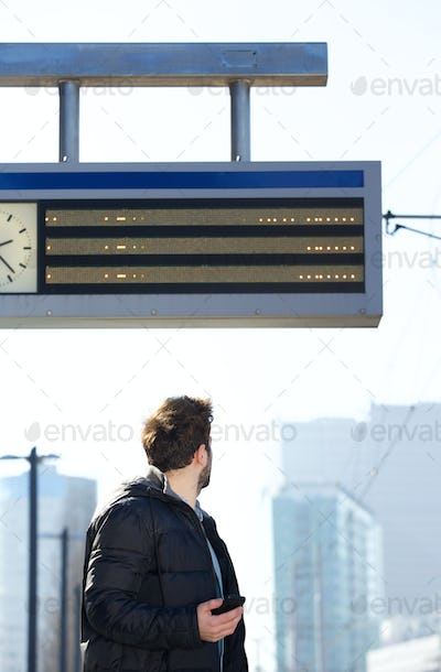 Young male traveler checking arrival time of train