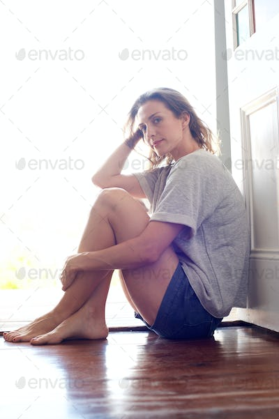 Beautiful woman sitting on wooden floor at home by doorway