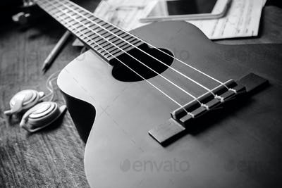 Ukulele guitar with earphone on wooden table