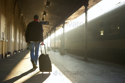 Man traveling with bag at train station