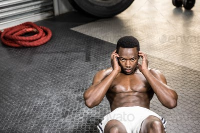 Muscular man doing abdominal crunches at the crossfit gym