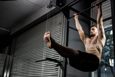 Shirtless man doing pull up at the crossfit gym