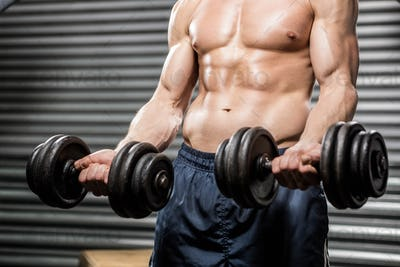 Shirtless man lifting heavy dumbbells at the crossfit gym