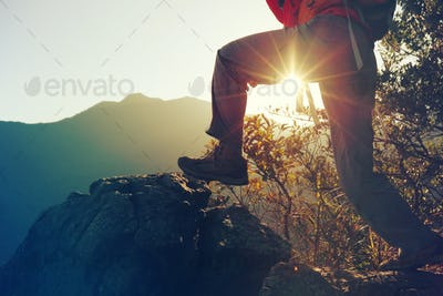 young woman hiker hiking on sunrise mountain peak