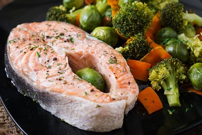 Cooked on steam salmon steak with vegetables.