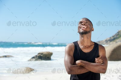 Happy young man laughing at the beach