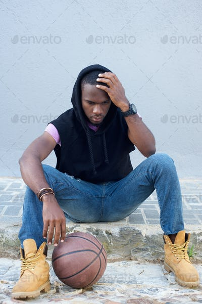 Young african american man sitting on sidewalk with basketball
