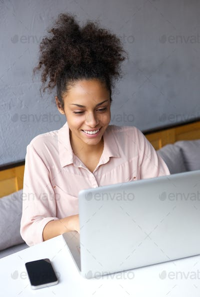 Happy young business woman working on laptop