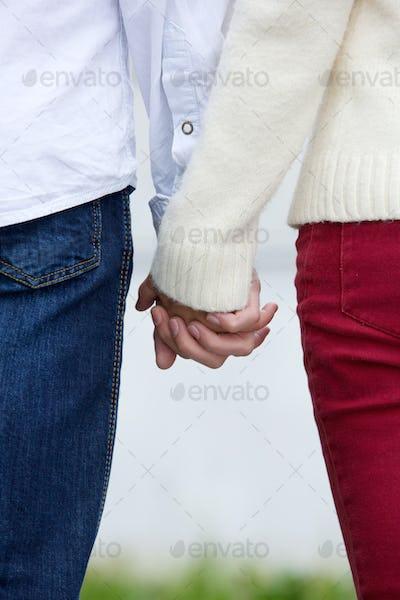 Boyfriend and girlfriend holding hands outdoors