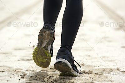 Woman feet running on sand